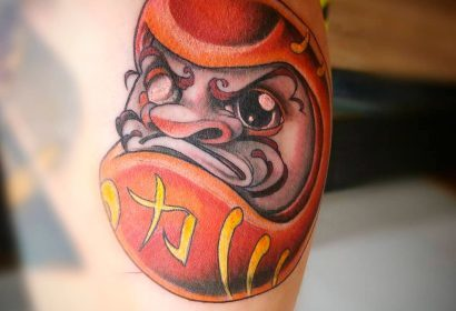 Tatuaje new school estilo cartoon a todo color de Daruma en gemelo chico. Tatuajes Cartoon & New School de Laura Bluntt en Ink Sweet Tattoo Madrid